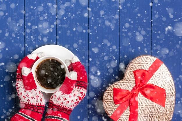 Kobiece dłonie z dzianinowymi rękawiczkami trzymają biały kubek z gorącą kawą americano i pudełko na niebieskim drewnie