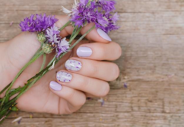 Kobiece dłonie z fioletowym wzorem paznokci