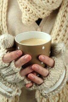 Kobiece dłonie z gorącym napojem, zbliżenie
