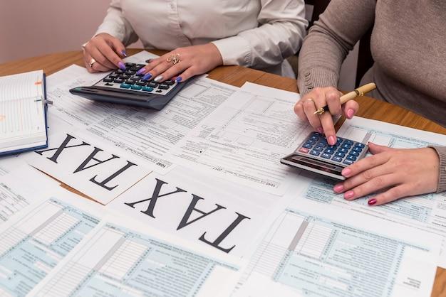 Kobiece dłonie z kalkulatorem i formularzem 1040