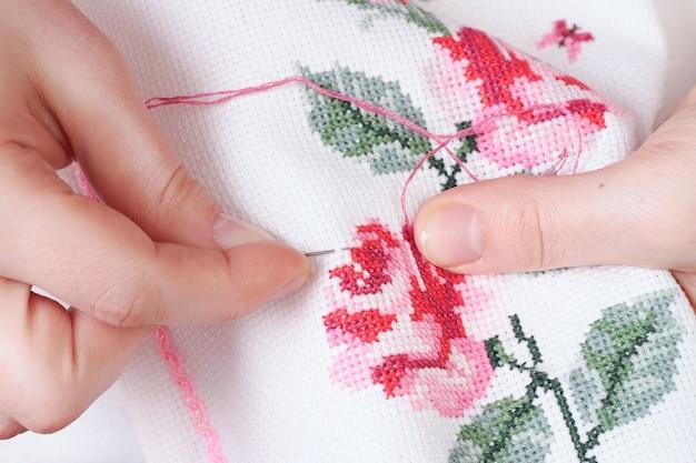 Kobiece dłonie z krzyżem wyhaftowanym na tkaninie wzorami kwiatów róż