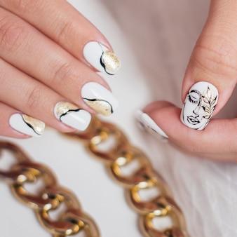 Kobiece dłonie z luksusowym manicure paznokciami złoty lakier żelowy