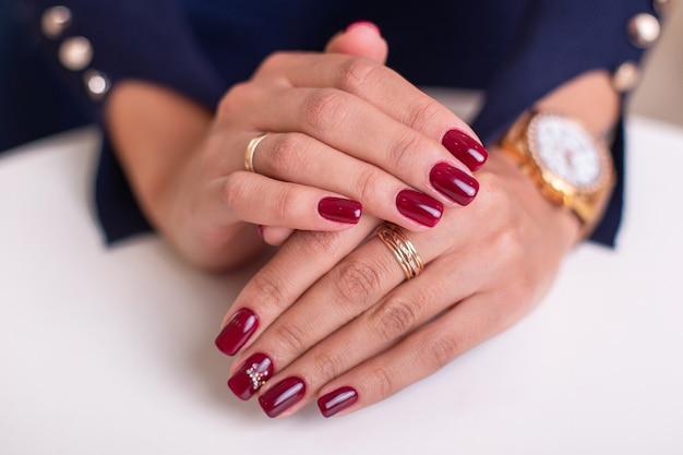 Kobiece dłonie z luksusowymi paznokciami do manicure, lakier żelowy czerwony wino na białym tle