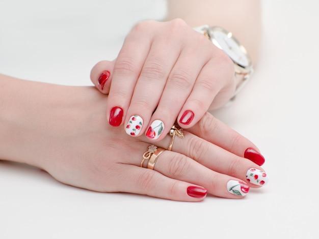 Kobiece dłonie z manicure, czerwony lakier do paznokci, rysunek z wiśniami