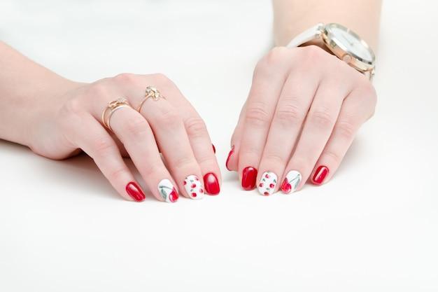 Kobiece dłonie z manicure, czerwony lakier do paznokci, rysunek z wiśniami.