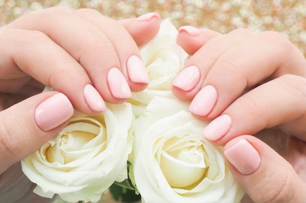 Kobiece dłonie z manicure i delikatnym różowym lakierem na paznokciach trzymają pąki białych róż.
