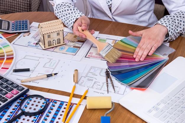 Kobiece dłonie z modelem domu i próbką koloru