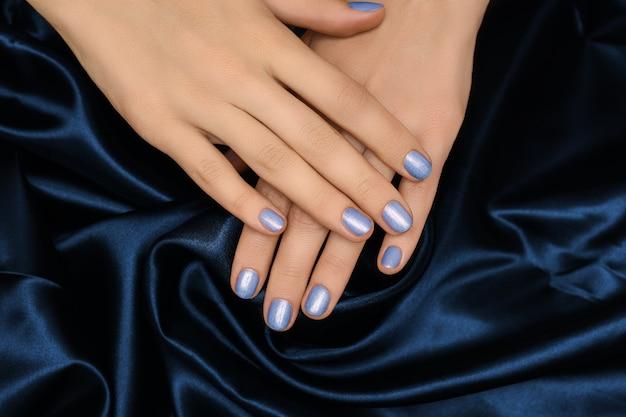 Kobiece dłonie z niebieskim wzorem paznokci. manicure do paznokci z niebieskim brokatem. kobieta ręce na tle niebieskiej tkaniny