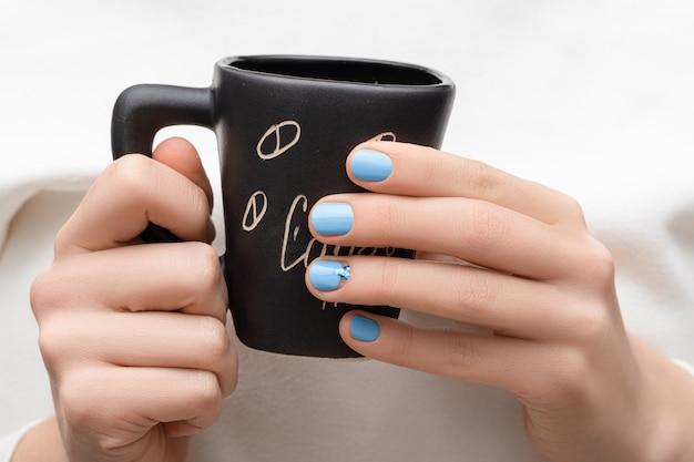 Kobiece dłonie z niebieskim wzorem paznokci trzymając czarny kubek kawy.