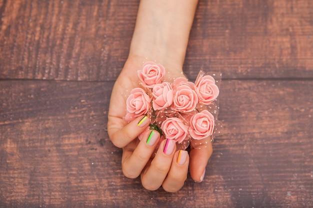 Kobiece dłonie z nowoczesnym manicure i różowymi kwiatami na mahoniu z odcieniem