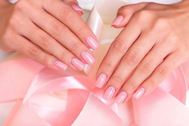 Kobiece dłonie z paznokci manicure na wstążkach