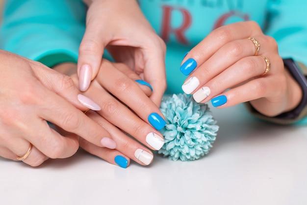 Kobiece dłonie z paznokci niebieski romantyczny manicure