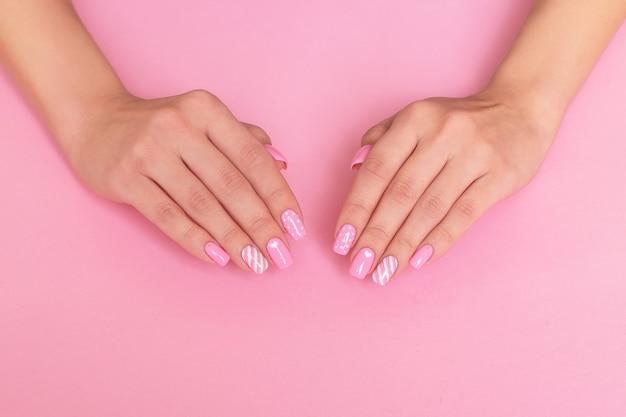 Kobiece dłonie z paznokci różowy manicure