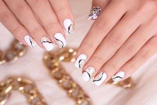 Kobiece dłonie z paznokci złoty manicure