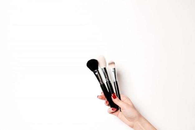 Kobiece dłonie z pędzelkami do makijażu i kosmetyków.