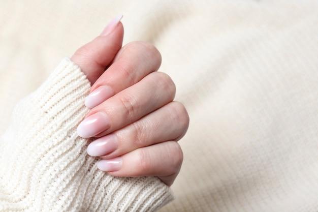 Kobiece dłonie z pięknym delikatnym białym zbliżeniem do manicure. kobiecy manicure do paznokci. luksusowy design paznokci na pięknych dłoniach kobiety.
