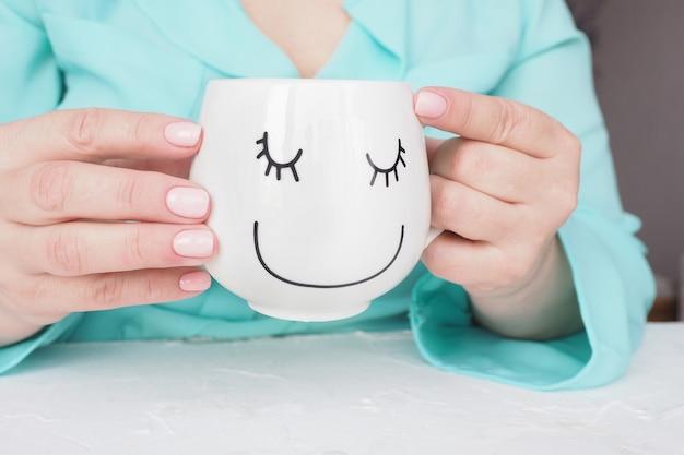 Kobiece dłonie z pięknym manicure i delikatnym różowym lakierem do paznokci trzymają kubek kawy lub herbaty z zabawną narysowaną twarzą