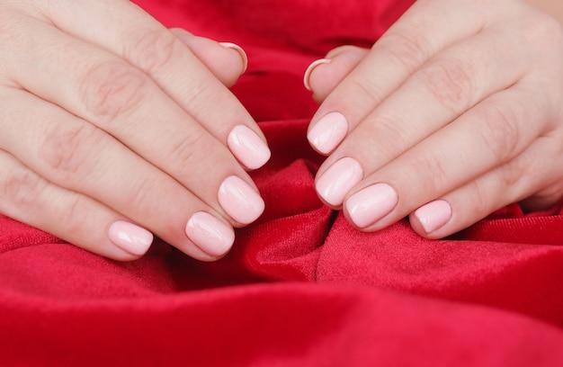 Kobiece dłonie z pięknym manicure i miękkim różowym lakierem do paznokci na pomarszczonym czerwonym aksamicie