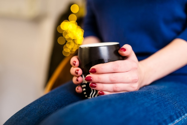 Kobiece dłonie z pięknym manicure trzymają filiżankę kawy