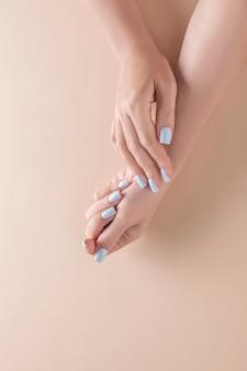 Kobiece dłonie z pięknym niebieskim manicure na jasnym tle, widok z góry.