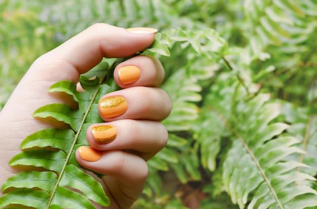 Kobiece dłonie z pomarańczowym wzorem paznokci.