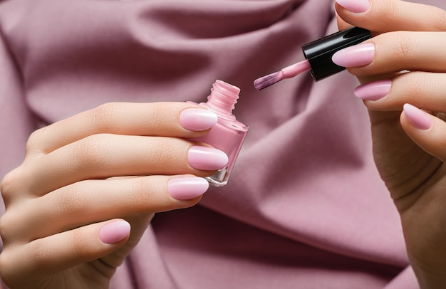 Kobiece dłonie z różany wzór paznokci, trzymając butelkę lakieru różanego i szczotka do paznokci