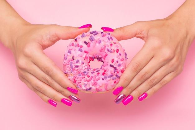 Kobiece dłonie z różowymi paznokciami do manicure trzymające słodkiego pączka truskawkowego