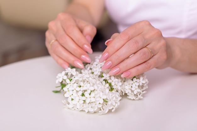 Kobiece dłonie z różowymi paznokciami do manicure