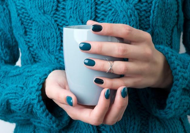 Kobiece dłonie z turkusowym manicure utrzymują szarą filiżankę kawy lub herbaty