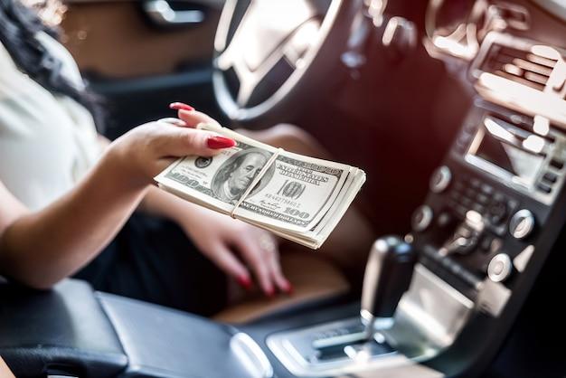 Kobiece dłonie z wiązką dolarów w samochodzie, zbliżenie