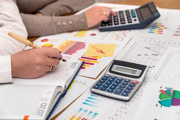 Kobiece dłonie z wykresami biznesowymi i kalkulatorami