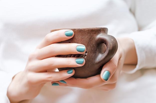Kobiece dłonie z zielonym wzorem paznokci trzymając kubek