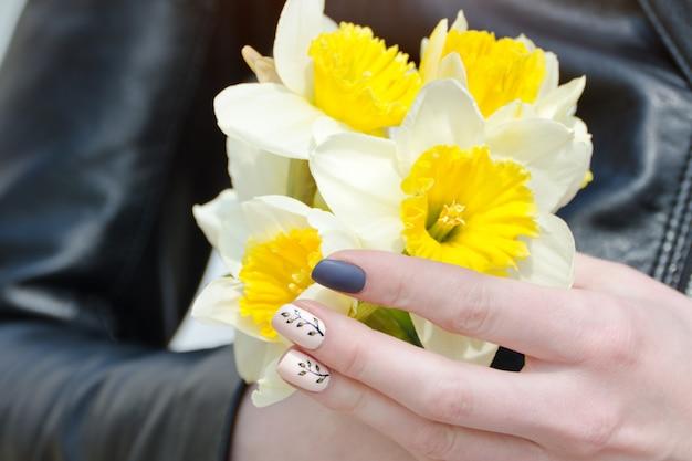 Kobiece dłonie z żonkilami, manicure. zbliżenie