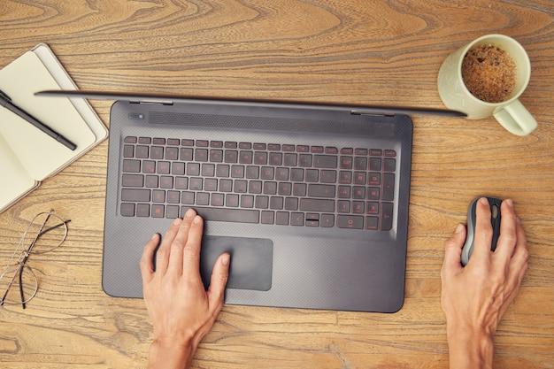 Kobiece dłonie za pomocą laptopa i myszy, na drewnianym biurku. towarzyszą filiżance kawy, notatnikowi i kieliszkom.