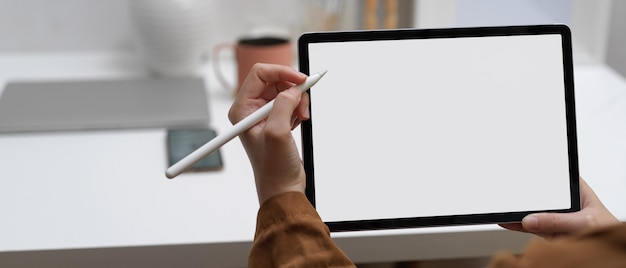 Kobiece dłonie za pomocą makiety tabletu z rysikiem, siedząc w domowym biurze