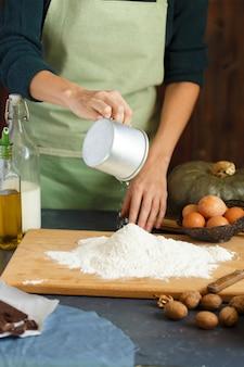 Kobiece dłonie zagniatają ciasto. cukiernik wbija jajko w mąkę. na drewnianym stole są składniki do pieczenia.