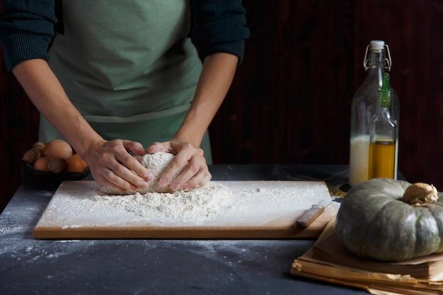 Kobiece dłonie zagniatają ciasto. wypiekowi składniki na drewnianym stole