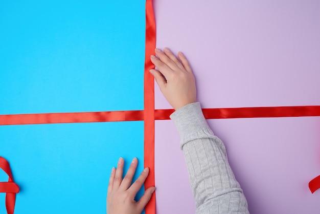 Kobiece dłonie zawiążą kokardę satynową czerwoną wstążką na pudełku