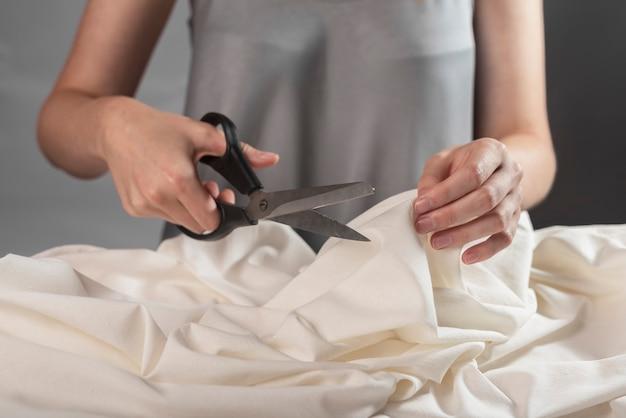 Kobiece dłonie zbliżenie cięcia pastelowej tkaniny z nożyczkami do szycia krawcowa w procesie pracy