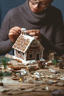 Kobiece dłonie zdobią świąteczny domek z piernika