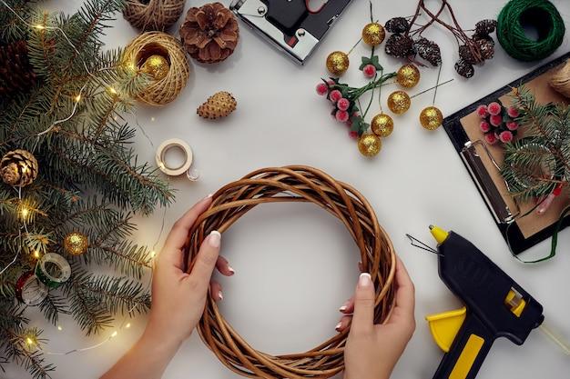 Kobiece dłonie zdobią świąteczny wieniec świerkowymi gałązkami z czerwoną jagodą i leśnymi szyszkami...