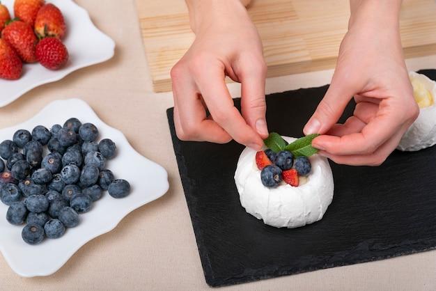 Kobiece dłonie zdobią tort. świeże jagody i widok z góry ciasto.