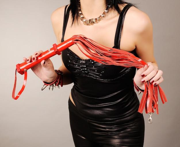 Kobiece dłonie ze skórzanym biczem