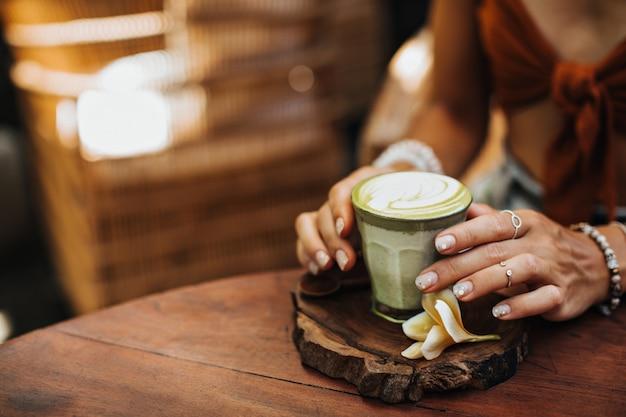Kobiece dłonie ze srebrnymi pierścieniami trzymają kieliszek matcha latte