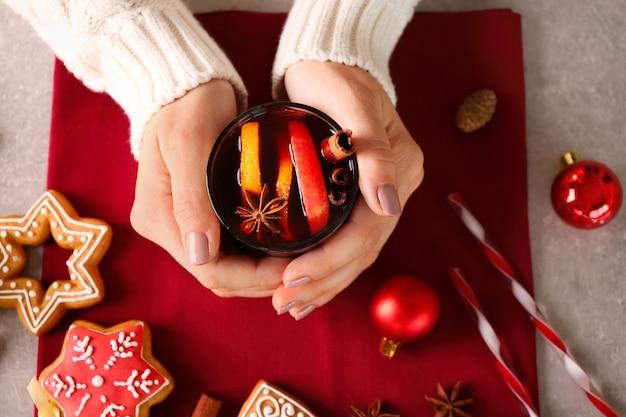 Kobiece dłonie ze szklaną filiżanką pysznego świątecznego grzanego wina na stole