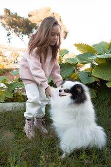 Kobiece dziecko i puszysty pies gra