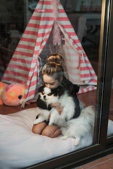 Kobiece dziecko przytulanie jej puszystego psa