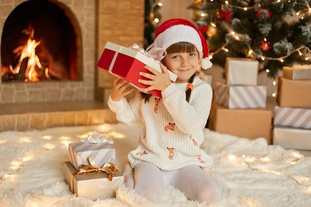 Kobiece dziecko w czerwonym kapeluszu i ciepłym białym swetrze siedzi na podłodze w salonie ze świątecznymi dekoracjami, potrząsając pudełkiem, próbując odgadnąć, co jest w środku.