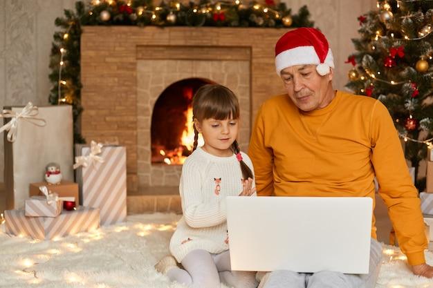 Kobiece dziecko z dziadkiem siedzi i korzysta z notebooka podczas bożonarodzeniowego poranka, patrzy na ekran, siedzi na podłodze przy kominku w przytulnym salonie, starszy mężczyzna w żółtej koszuli i czapce mikołaja.