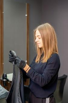 Kobiece fryzjer przygotować stawia na czarną pelerynę na klientce w salonie piękności